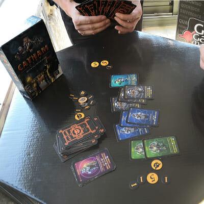 Au centre de la table, les différentes factions disponibles au recrutement et la pioche face cachée ainsi que la défausse.