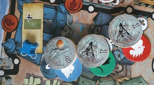 Les Clans rouge (Marfaux) et vert (Malingreux) ont la même force de combat. C'est le joueur le plus proche de la croix blanche (à droite) qui remporte l'Affrontement. Le joueur rouge posera donc son pion Renommée à la place de celui du joueur bleu (Orphelin) dans le cartouche du quartier)