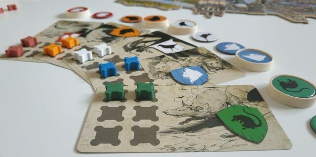 Les 5 clans (Malingreux, Orphelins, Millards, Narquois et Marfaux) avec leurs plateaux personnels, leurs pions Renommée et Ribauds