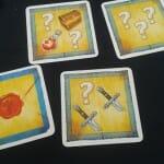 Quelques exemples de cartes Secret qui vous disent comment plier votre mouchoir. Par exemple, la carte du bas exige de ne laisser paraître que 3 symboles, dont 2 épées. Regardez un peu le mouchoir ci-dessus et tentez donc le coup. (Réponse en bas de l'article).